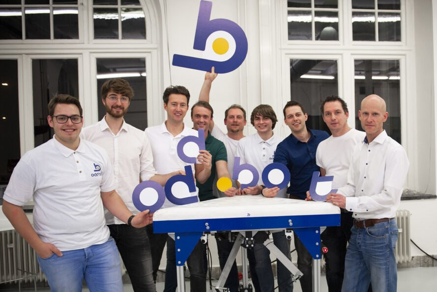 "a group of people in white shirts (the Odd.Bot team), holding cutout letters that spell ""Odd.Bot"""
