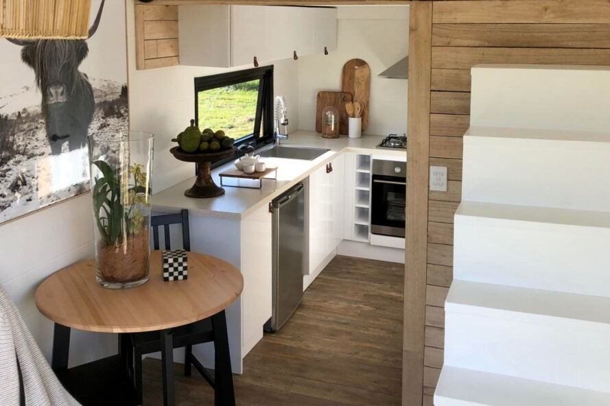 white kitchen of tiny home with stairs leading up to sleeping loft