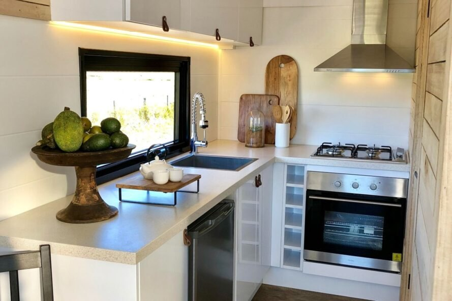 tiny home kitchen with white cabinets and full-sized stove