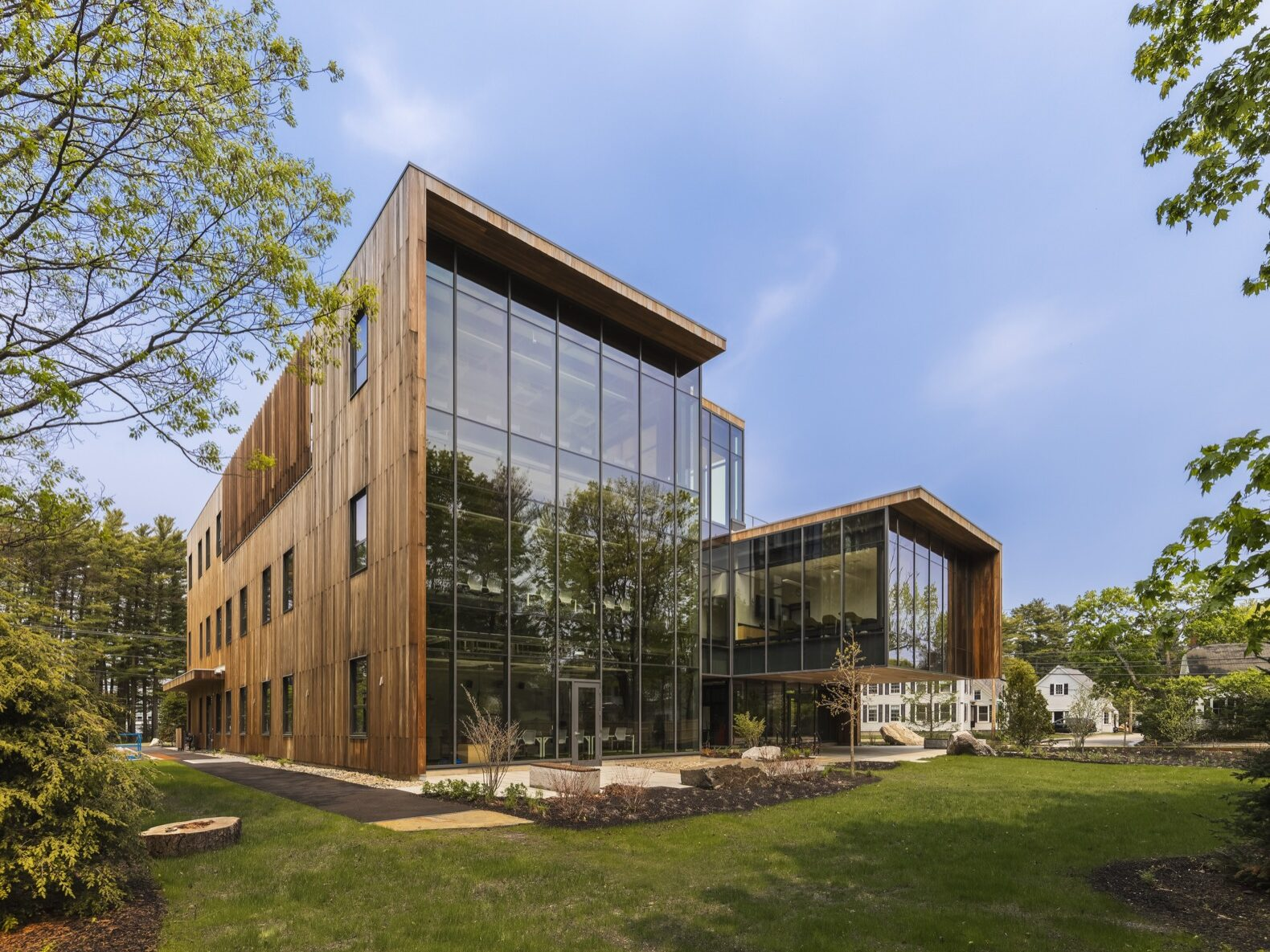 a large glass facade building surrounded by wood panels
