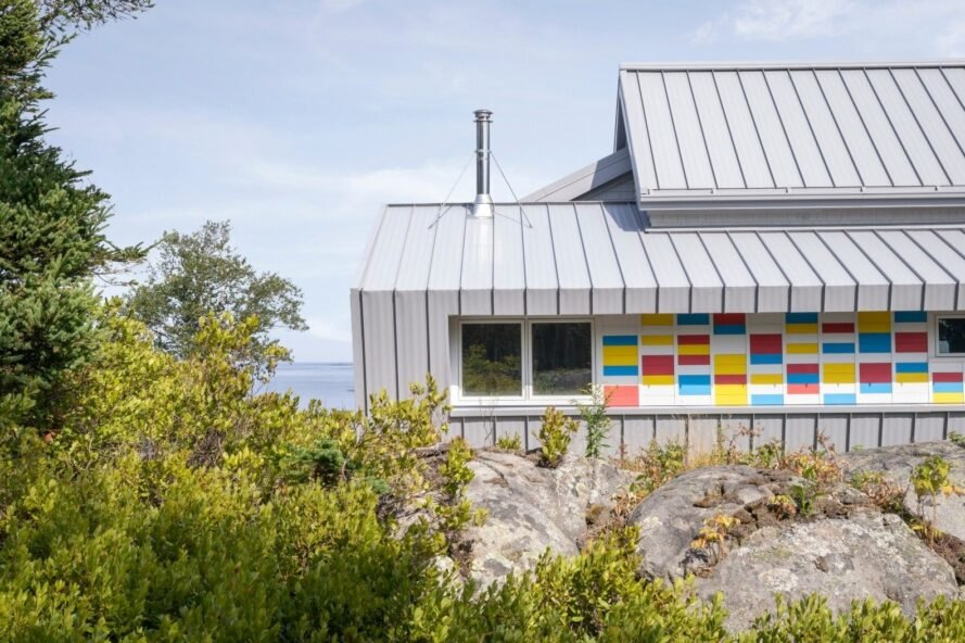 white home with dual pitched roofs and colorful siding