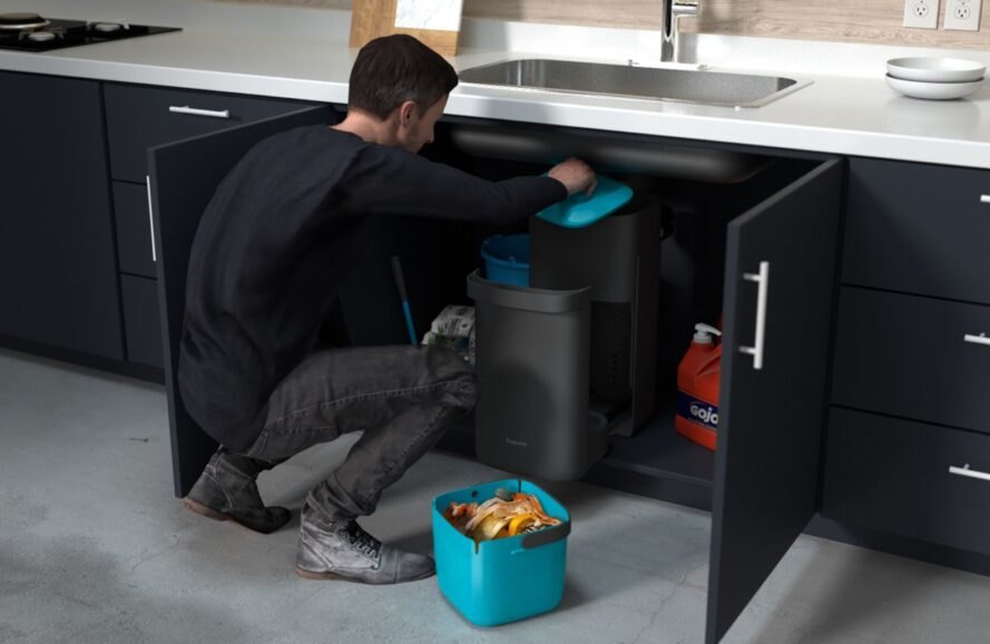 person emptying gray compost bin located under a sink