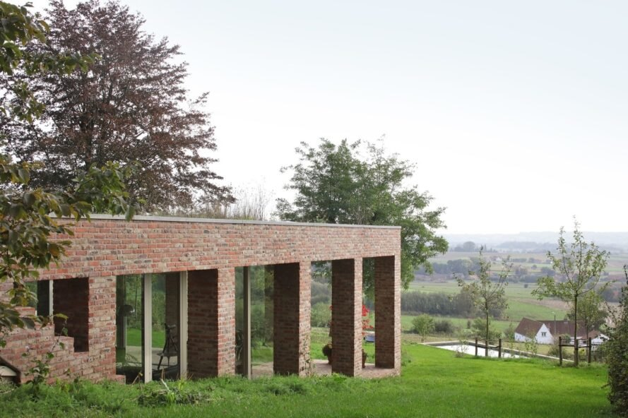 brick home built into green slope