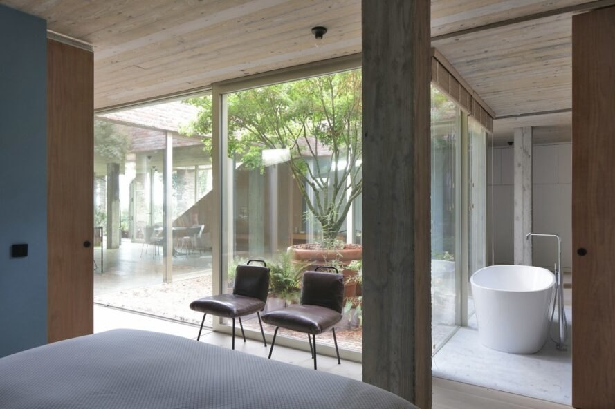 bed facing glass walls with views of a courtyard