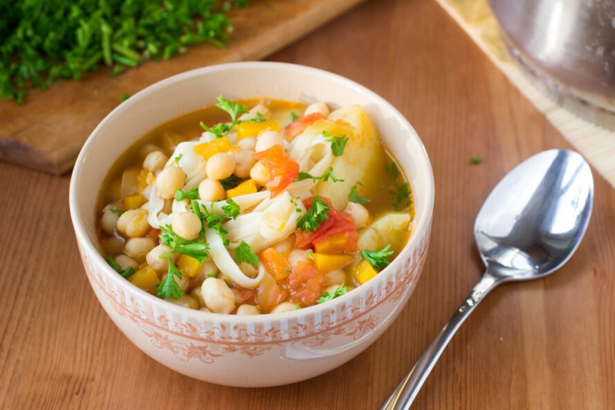 vegan chickpea noodle vegetable soup in white bowl