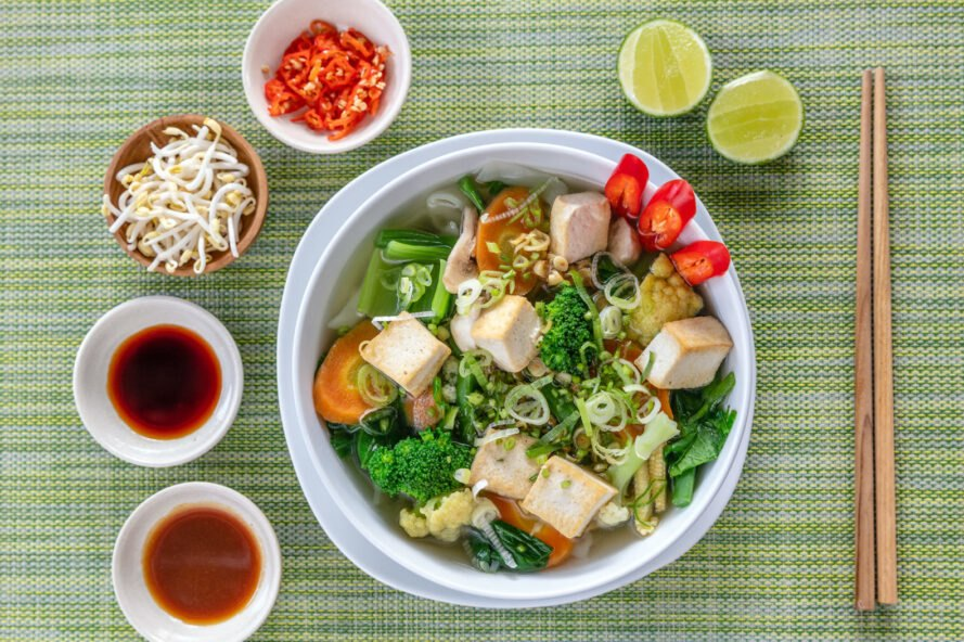 vegan pho and fresh toppings on a green background