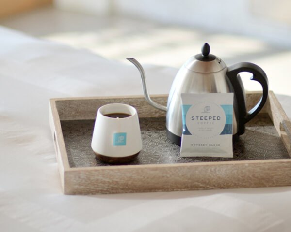 kettle, mug and package of a coffee bag on a tray on a hotel bed