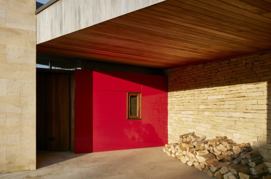 a red entranceway with a pile of wood stacked off to the side