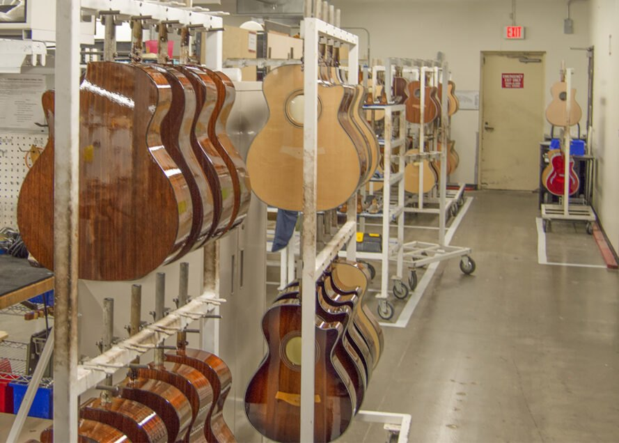 racks of guitars hanging up in a storage room