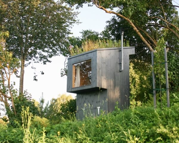 black outhouse with grassy roof