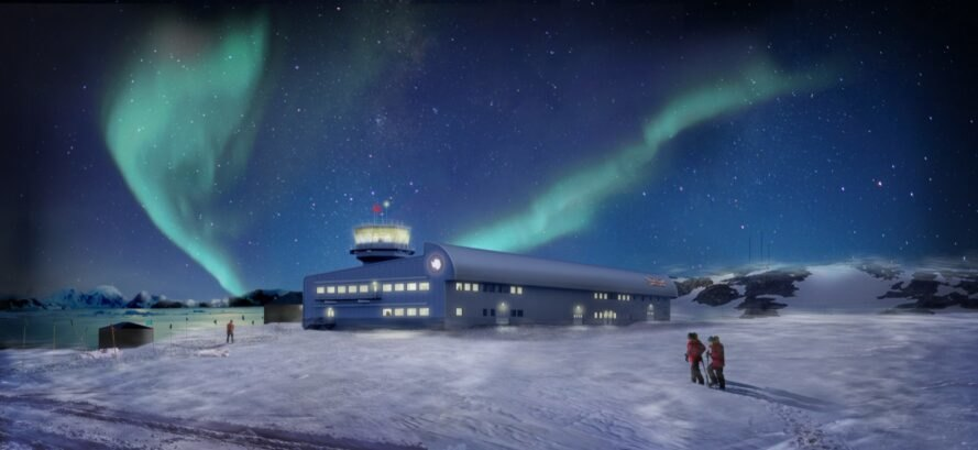 long blue building in snowy Antarctic landscape under an aurora in the sky