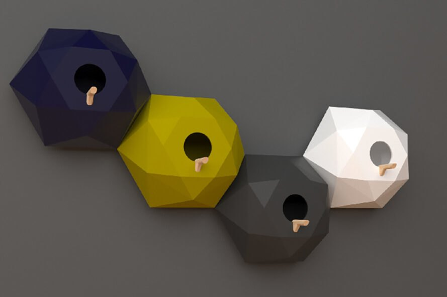 four geometric birdhouses on a gray wall. from left to right, the birdhouses are dark blue, yellow, gray, and white