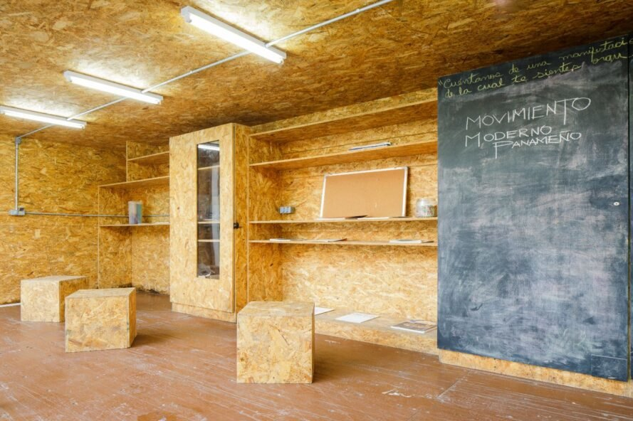 museum interior room with walls made of particle board and a huge chalkboard