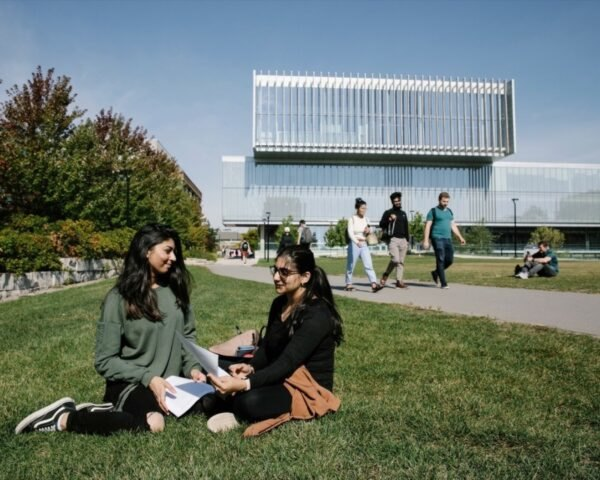 students sitting in grassy area in front of large glass building