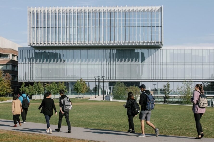 students walking on path outside large glass building