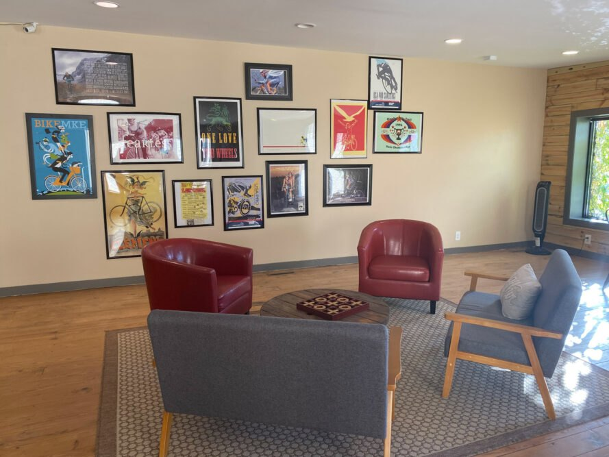 seating area with red and gray chairs and bike-related framed art on the wall