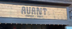 "Coffee shop with a black and wood sign that reads, ""Avant Coffee Bikes"""