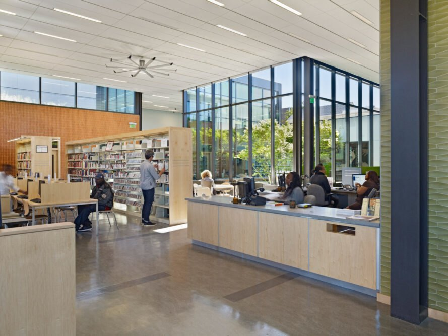 reception desk in a bright library with walls of glass