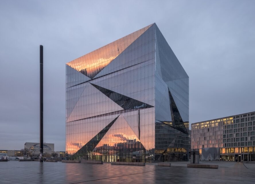 cube building with mirrored facade reflecting a sunset