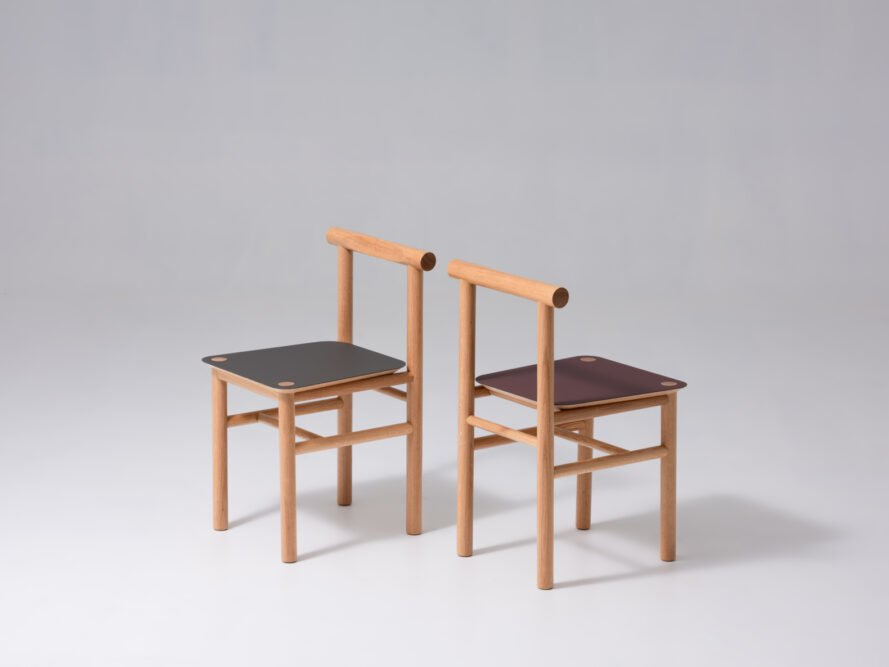 two oak wood chairs with black and red seats
