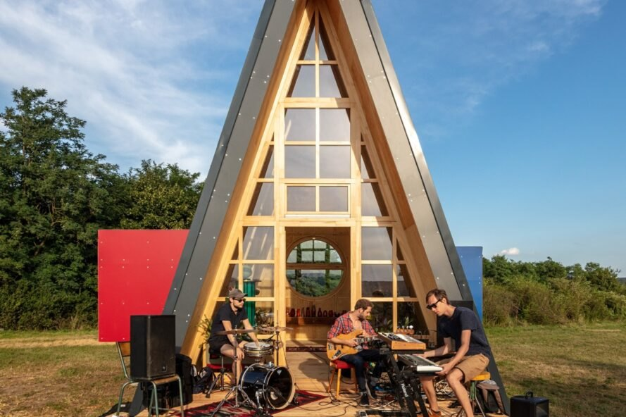 group of musicians jamming outside a triangular cabin