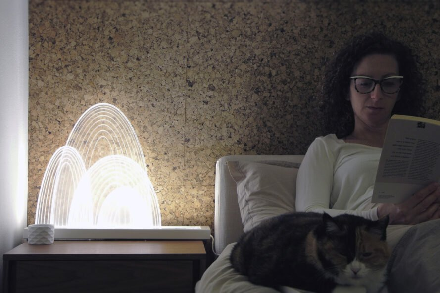 white LED light lamp on a nightstand beside a person reading in bed