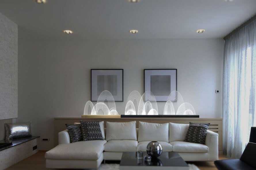 several curved white lamps on a table in a modern living room