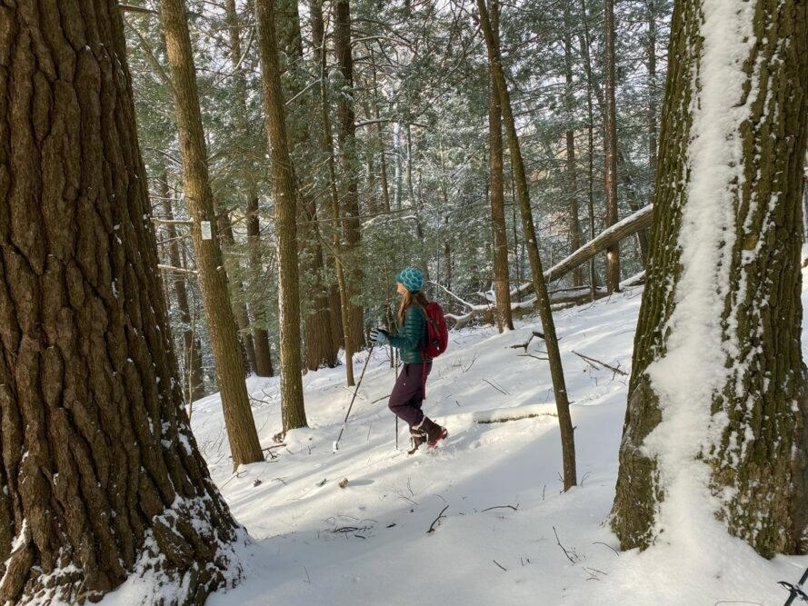 person snowshoeing downhill in a snowy landscape