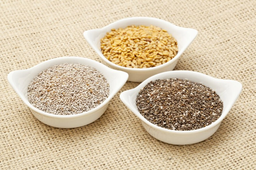 chia and flax seeds in white bowls on burlap