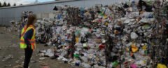 person stands next to piles of plastic at a recycling plant