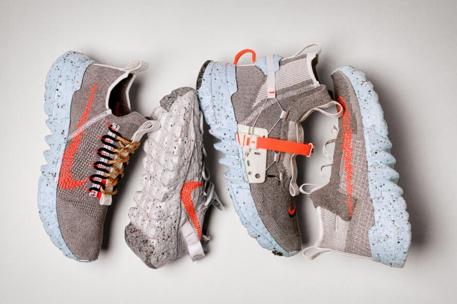 four gray sneakers with orange designs on the sides