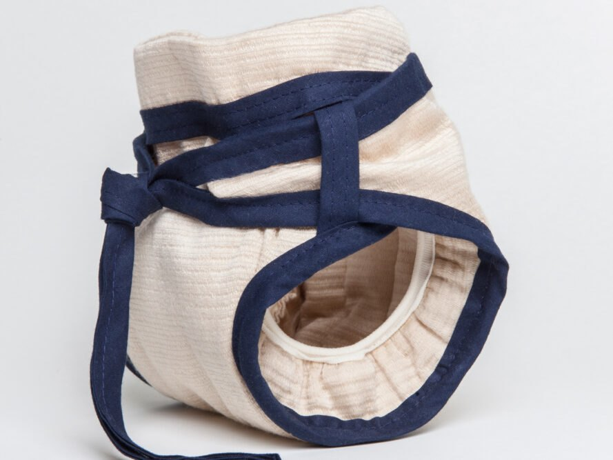 side view of tan reusable diaper with blue ties around the waist