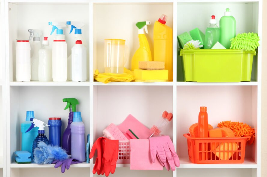 white shelves filled with colorful plastic bottles of household cleaners