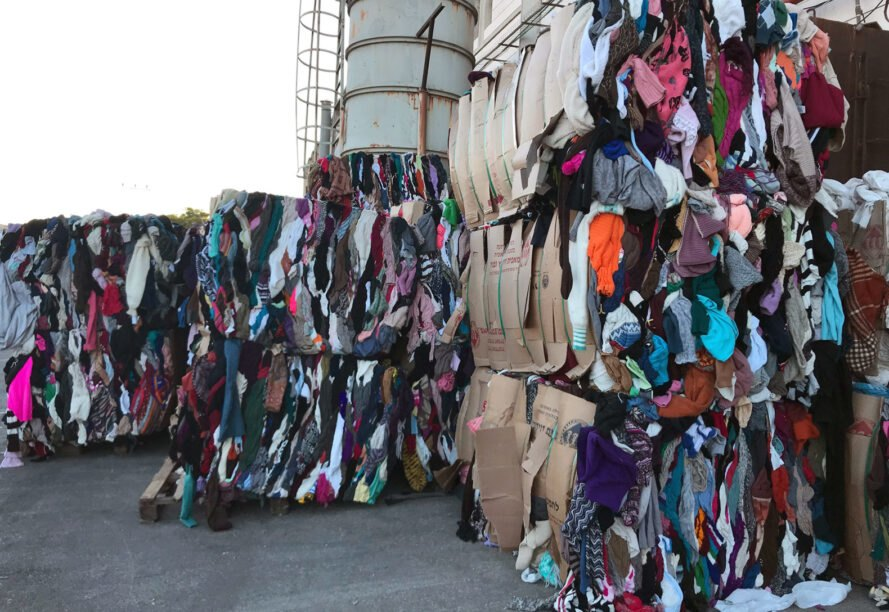 stacked of bounded recycled clothes at a landfill