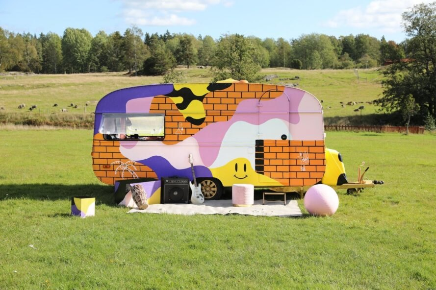 a multi-colored campervan with various instruments on the ground