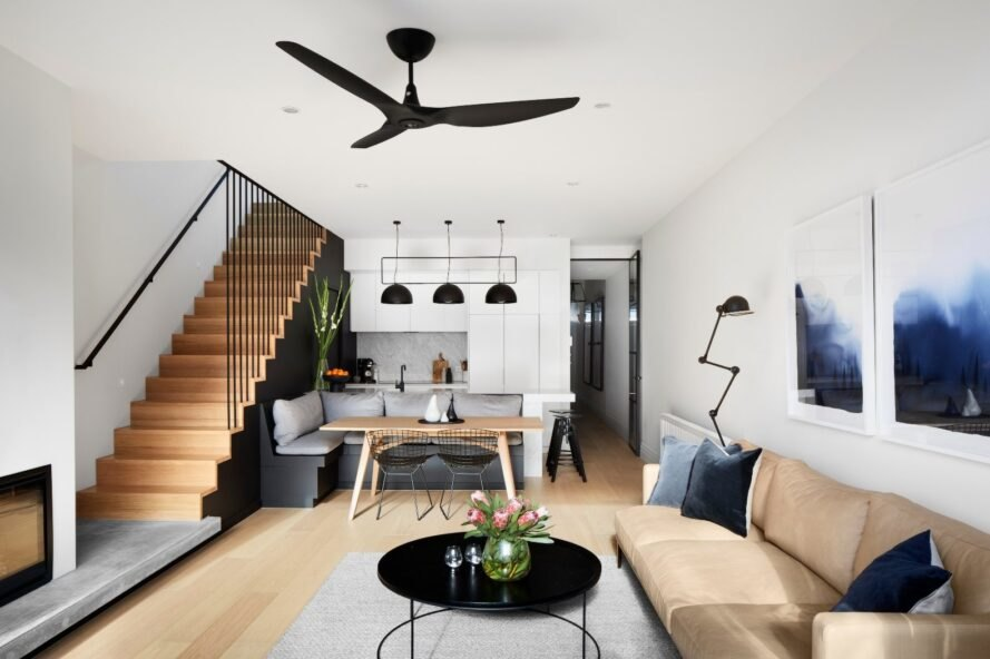 tan sofa, black round coffee table and wooden staircase