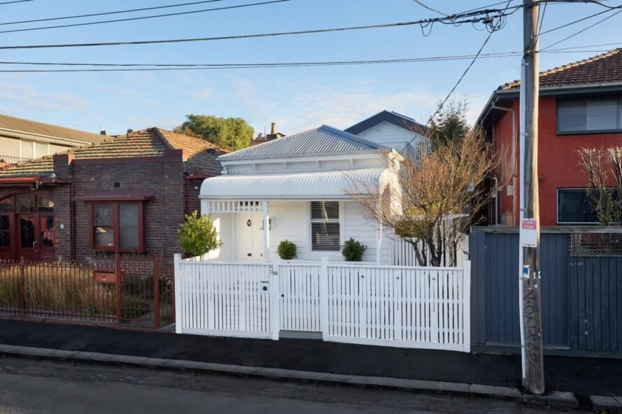 white cottage house with white picket fence