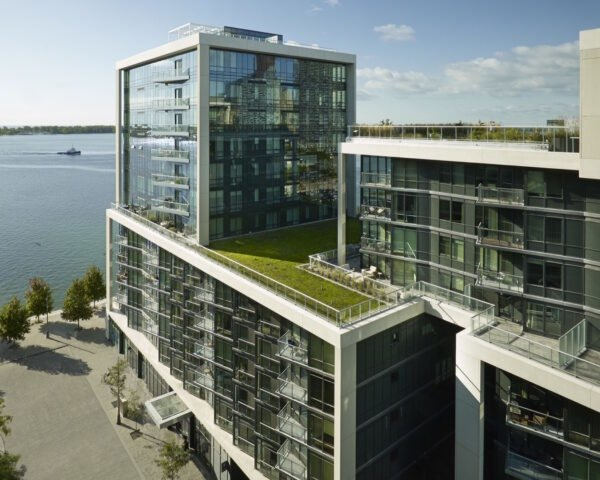 condo building with glass walls and a green roof