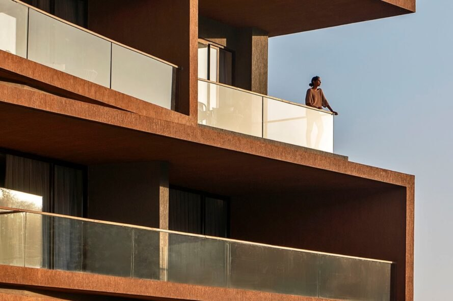 man standing out on balcony with glass balustrades
