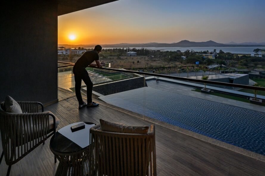 man looking out onto swimming pool