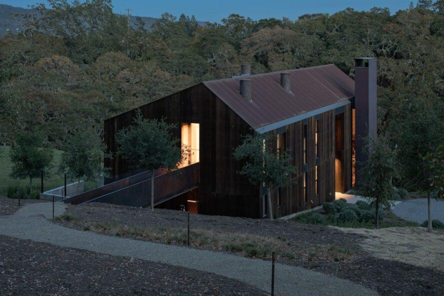 evening shot of large wood home with pitched roof