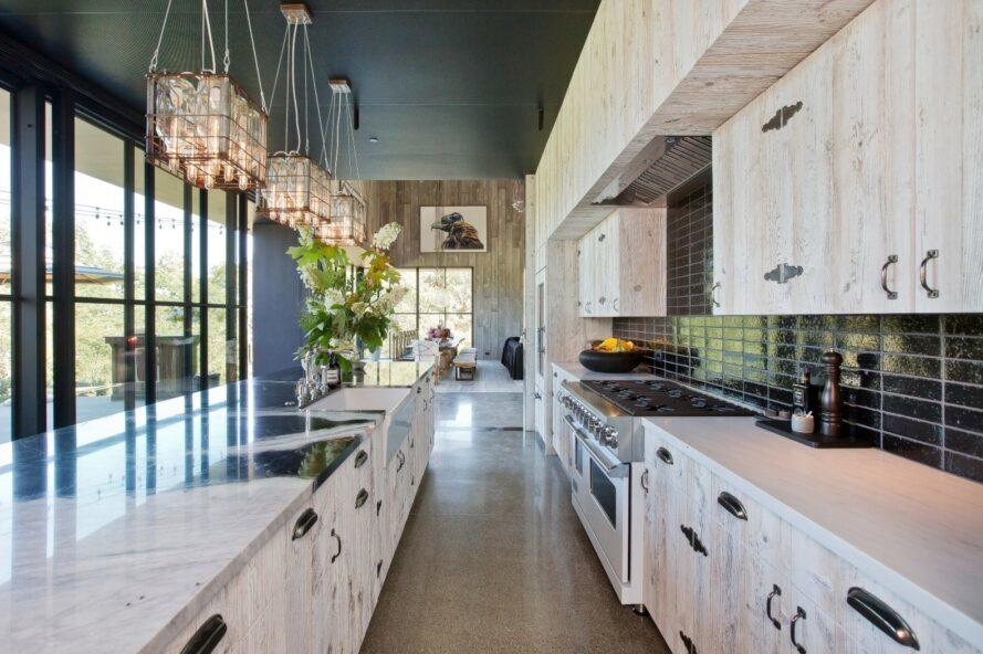 large kitchen with pendant lights and white cabinets and island