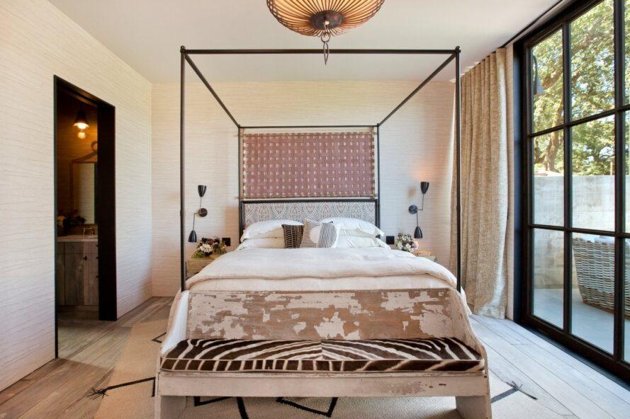 white four-poster bed with patterned bench at the foot