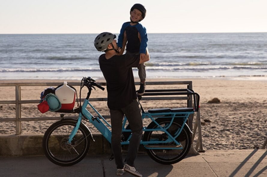 a blue electric bike with a dad and son standing next to it in helmets. in the background is a beach