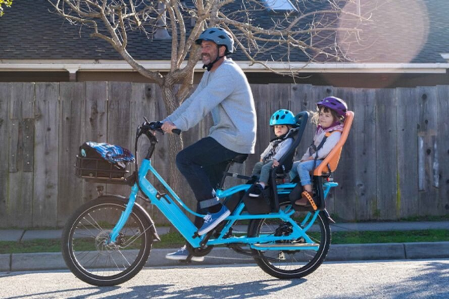 a blue electric bike with a dad at the front and two children sitting towards the back