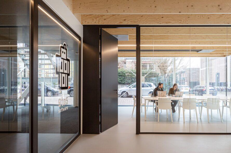 black door leading to meeting room with glass walls