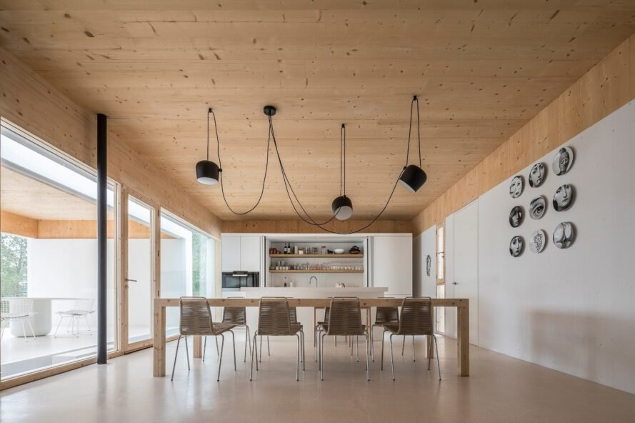 white room with wood ceilings and large wood dining table