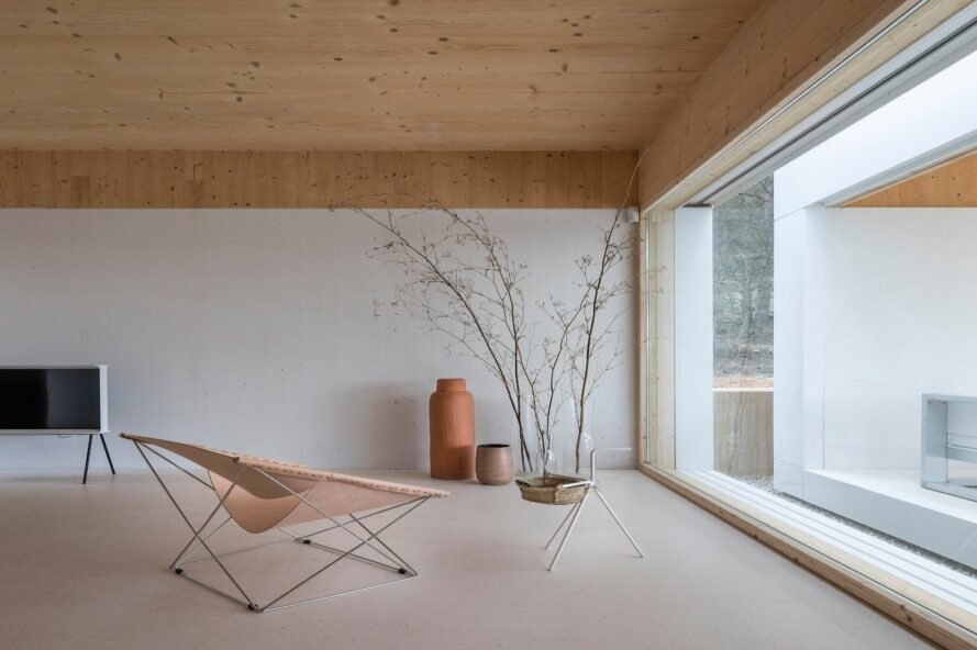 minimalist living space with one chair facing a glass wall