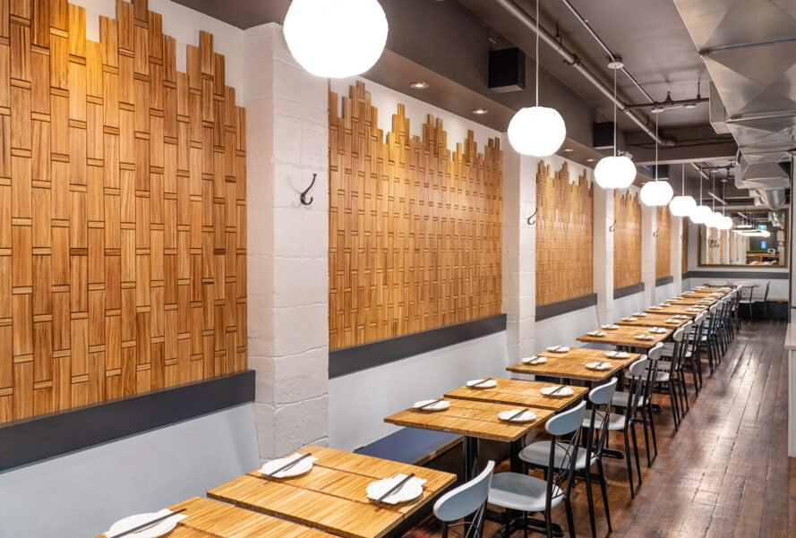 restaurant with wood tables and wood walls made from chopsticks