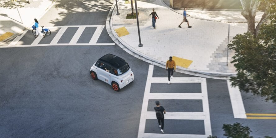 tiny gray electric car waiting as people cross at a crosswalk